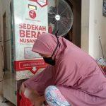 seorang ibu sedang menuangkan sedekah beras