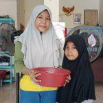 dua anak perempuan menerima sedekah beras